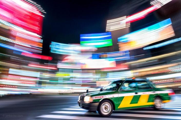 Colorful neon billboards and taxi at the Shibuya Crossing in Tokyo, Japan