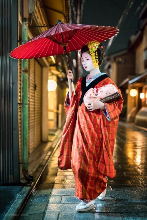 Maiko with red umbrella in the Gion district of Kyoto, Japan