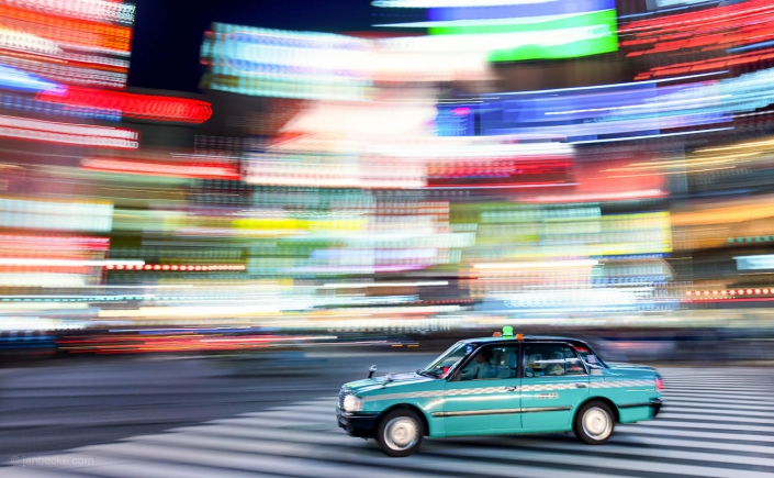 Taxi passing by the colorful neon billboards at night in the Shibuya district