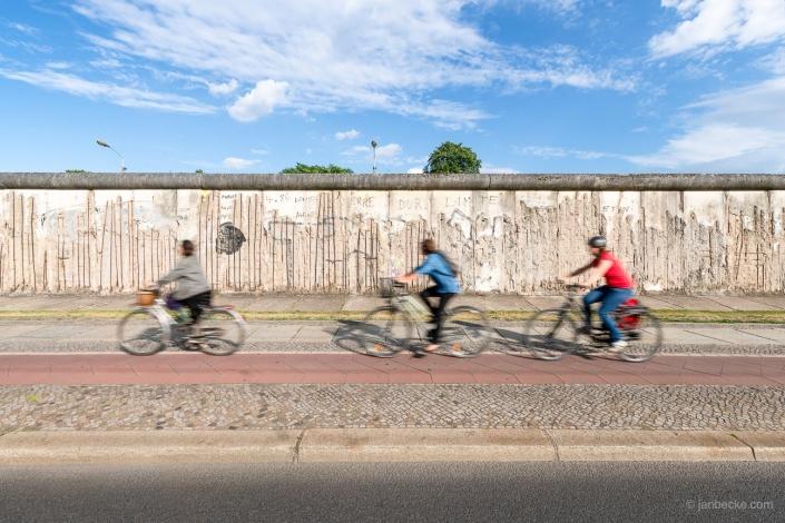 A group of cyclist driving along the Berlin Wall near Bernauer Straße