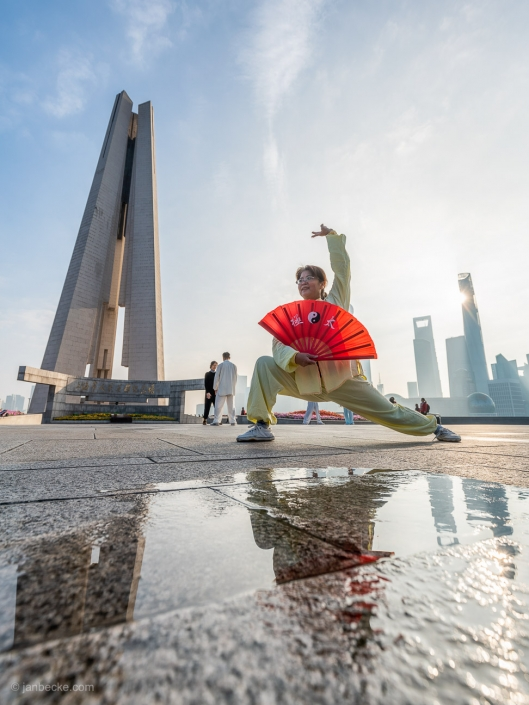Chinese woman performing Tai Chi at the Bund promenade in Shanghai