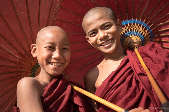 Two young Burmese monks with red umbrellas smiling, Myanmar
