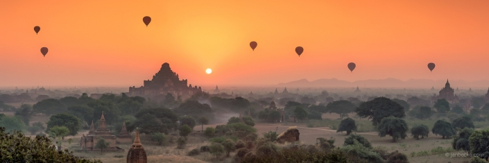 Hot-air balloons over Bagan durin sunrise with panoramic view of Dhammayangyi Temple
