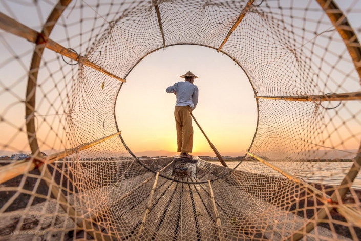 Traditional Intha fisherman on the Inle Lake during sunset