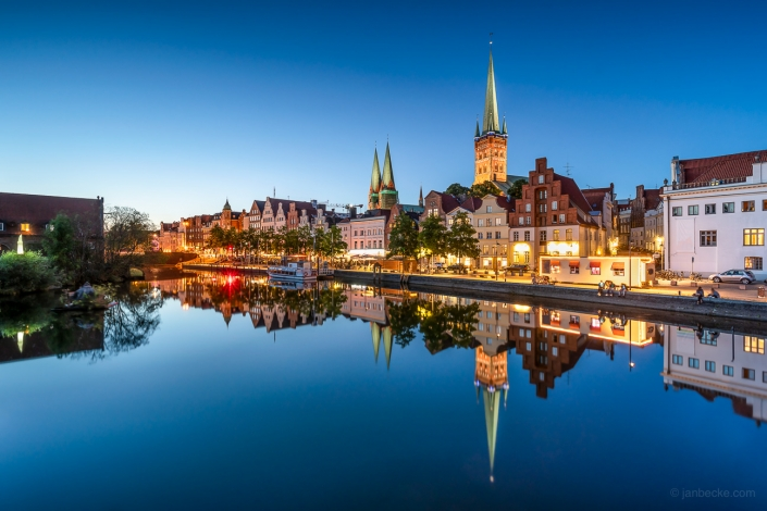 Old town of Lübeck at night with reflection of the skyline in the Trave river