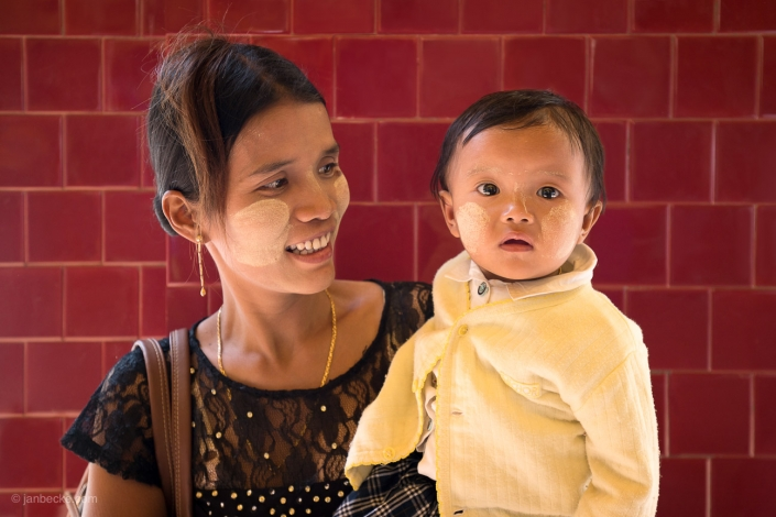 Young Burmese woman with her baby child both with Thanaka paste on their face