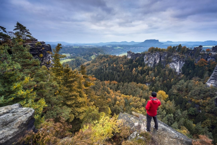 Tourist standing on a rock in Saxon Switzerland in autumn, Germany
