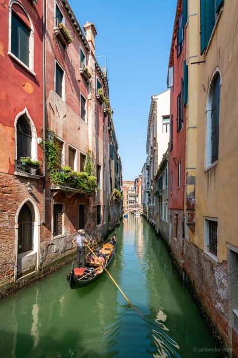 Romantic gondola ride along a small canal in Venice, Italy