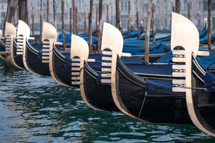 Gondolas at the pier in Venice with ferro di prua ornament