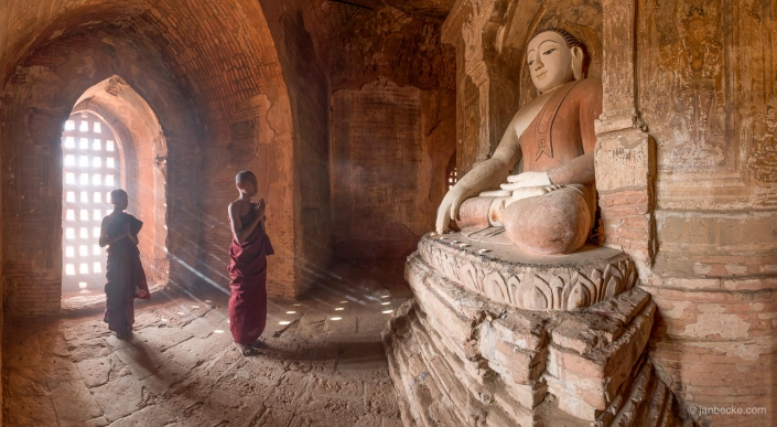 Buddhist monks praying in front of large buddhist statue in Bagan, Myanmar
