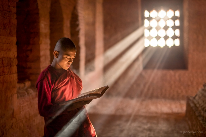 Burmese buddhist monk reading a book at a temple in Bagan, Myanmar