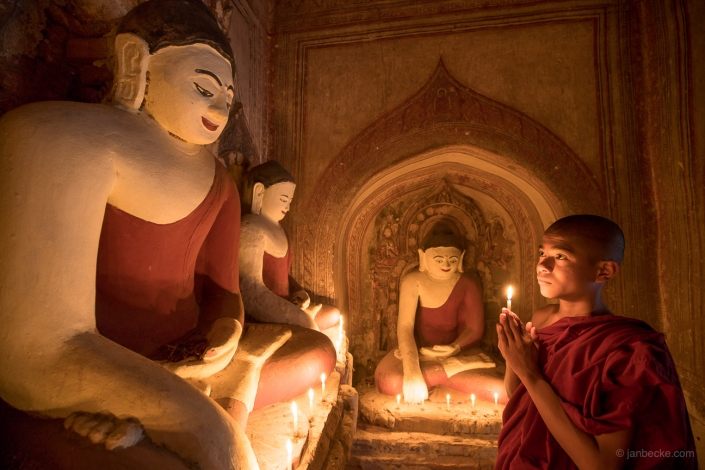 Young Burmese buddhist monk praying at a temple in Bagan, Myanmar