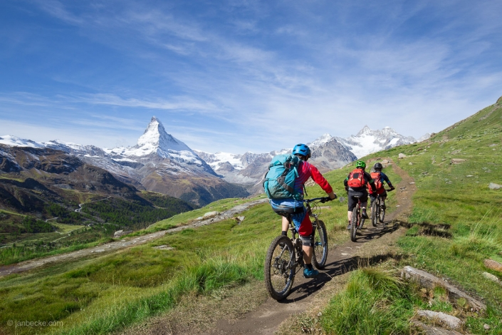 Group of downhill mountain bikers in front of the Matterhorn peak, Swiss alps