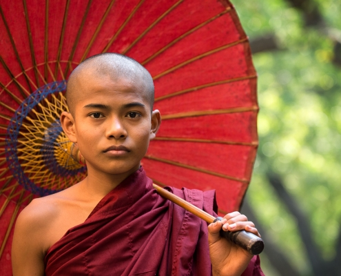 Young burmese Monk with red umbrella in Bagan, Myanmar