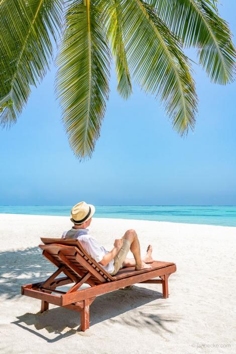 Young man taking a relaxing sunbath in a beach chair