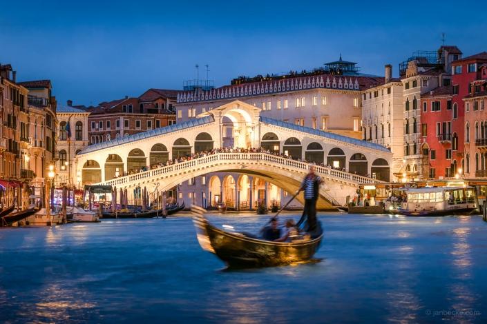 Gondola with tourists near the Rialto Bridge in Venice, Italy