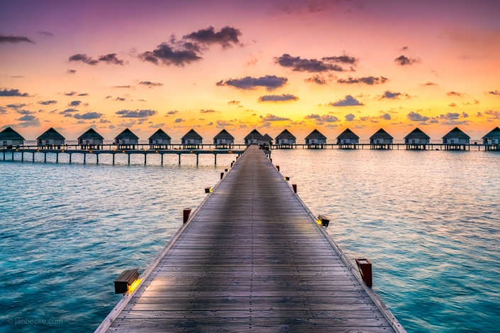 Sunset at a luxury beach resort with overwater villas, South Ari Atoll, Maldives