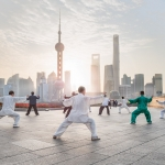 A group of Chinese people performing Tai Chi exercises at the Bund promenade in Shanghai, China