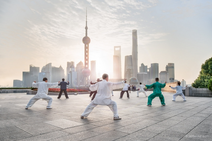 A group of Chinese performing Tai Chi exercises at the Bund in Shanghai