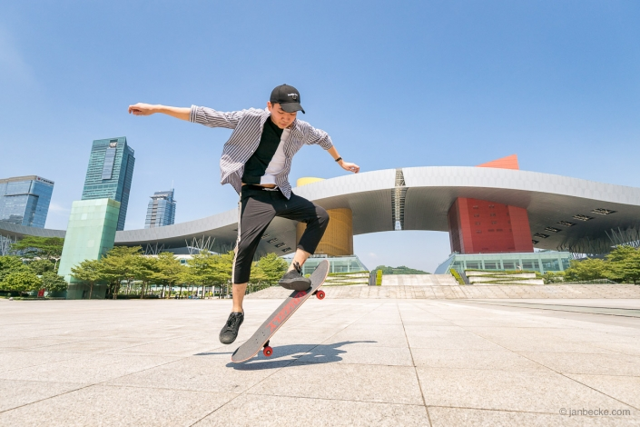 Young Chinese skater in front of Shenzhen Civic Center performing the ollie skateboarding trick