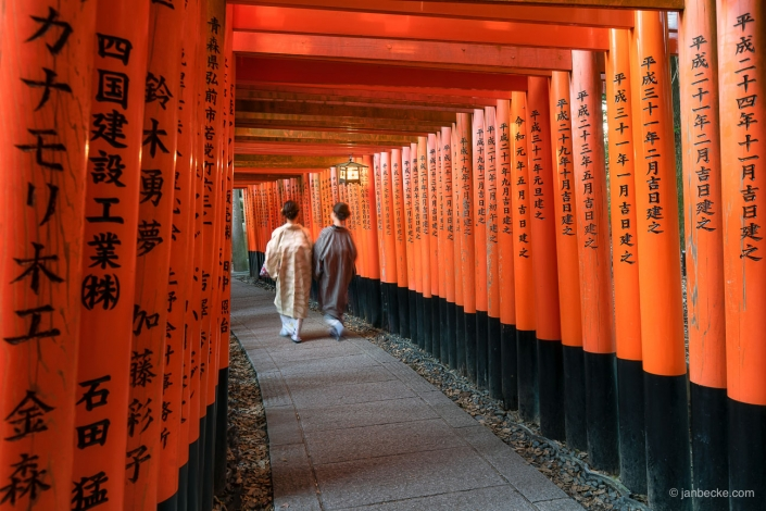 Two Japanese women in Kimono walking along the tunnel of red torii gates at the Fushimi Inari Shrine in Kyoto